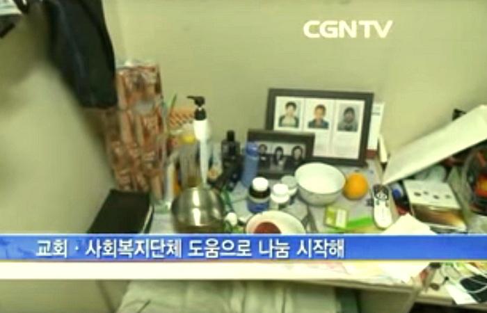 사진: 기부 천사 김우수가 거처하던 고시원의 CGNTV의 방송장면. 소박한 식사식기와 후원했던 아이들의 사진이 같이 있다. 이 작은 공간에서 아이들을 생각하며 살았다. [기부천사 중국집 배달원의 삶]