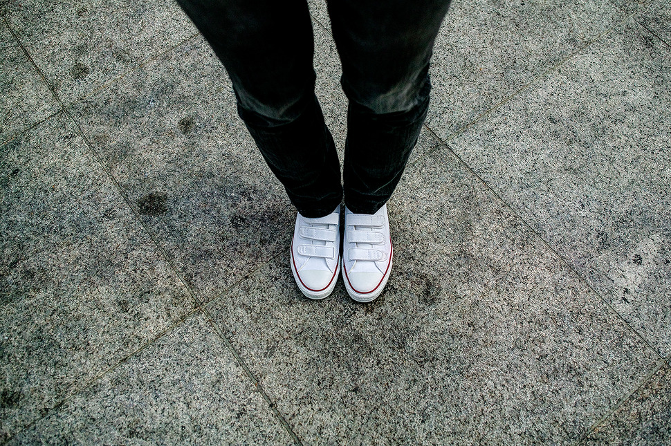 검정색 스키니진에 하얀색 새 신발을 신고있는 사진.